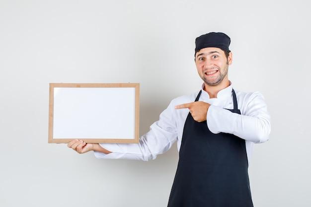 Chef masculino apontando para um quadro branco de uniforme, avental e olhando alegre. vista frontal.