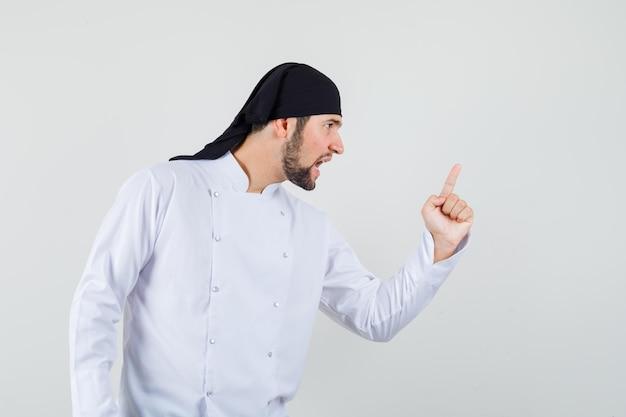 Chef masculino avisando alguém com o dedo no uniforme branco e parecendo nervoso. vista frontal.