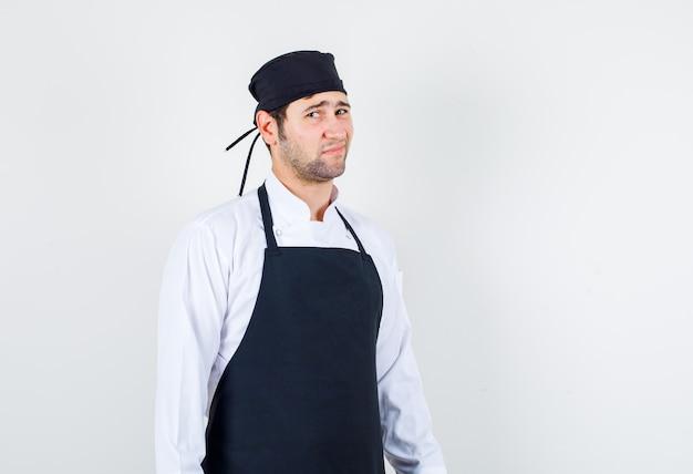 Chef masculino com cara carrancuda de uniforme, avental e olhando descontente, vista frontal.