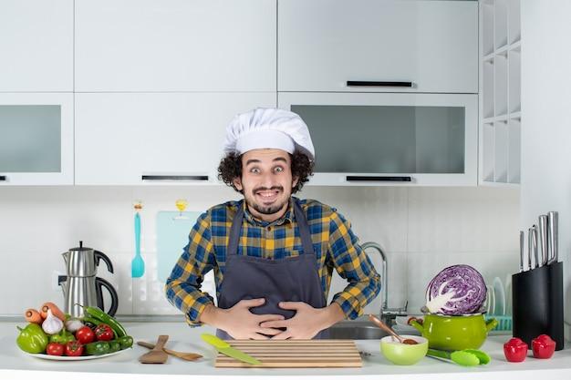 Chef masculino com legumes frescos e cozinhando com utensílios de cozinha e sofrendo de dor de estômago na cozinha branca