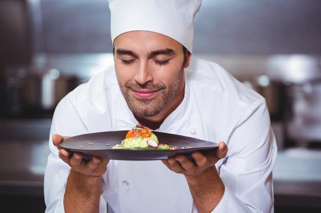 Chef masculino com os olhos fechados comida cheirosa