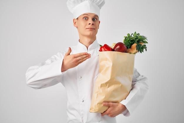 Chef masculino com pacote de comida na cozinha de comida saudável