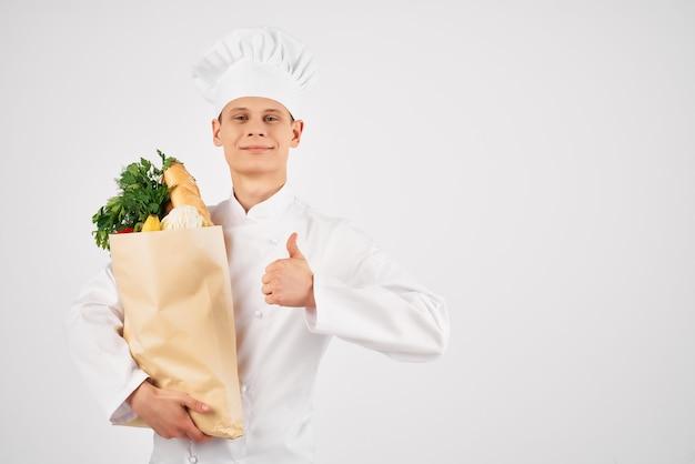 Chef masculino com um pacote de comida em um restaurante de mercearia.