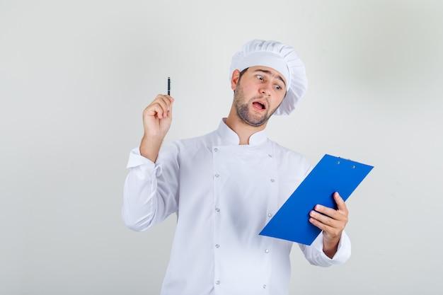 Chef masculino com uniforme branco segurando caneta e prancheta e parecendo ocupado