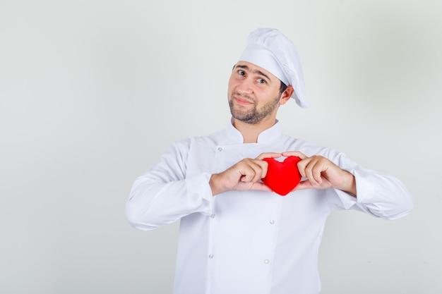 Chef masculino com uniforme branco segurando um coração vermelho e parecendo feliz