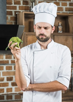 Chef masculino contemplada segurando brócolis orgânicos verdes na mão