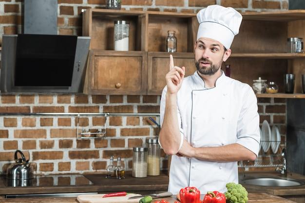 Chef masculino contemplado na cozinha, apontando o dedo para cima