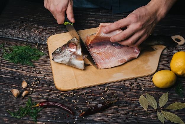 Chef masculino corta peixe vermelho fresco em uma placa em uma mesa de madeira