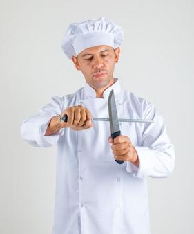 Chef masculino cozinhar de uniforme e chapéu segurando facas de cozinha e olhar confiante