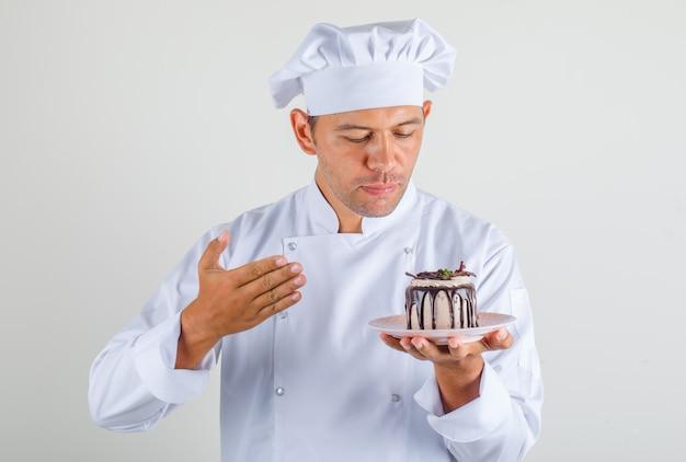 Chef masculino cozinhar no chapéu e uniforme, olhando para o bolo na mão e olhando orgulhoso