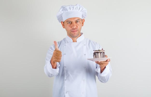 Chef masculino cozinhar no chapéu e uniforme segurando o bolo e mostrando os polegares