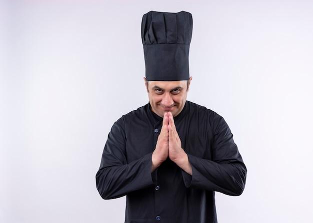 Chef masculino cozinheiro vestindo uniforme preto e chapéu de cozinheiro de mãos dadas, sentindo-se grato em pé sobre um fundo branco