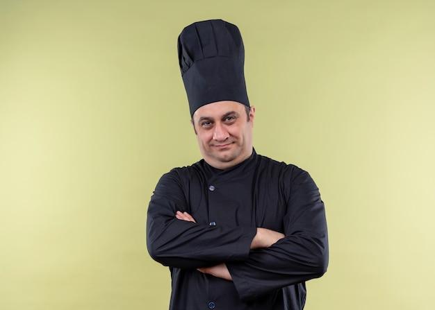 Chef masculino cozinheiro vestindo uniforme preto e chapéu de cozinheiro olhando para a câmera com as mãos cruzadas, parecendo confiante em pé sobre um fundo verde