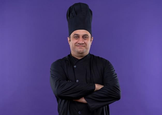Chef masculino cozinheiro vestindo uniforme preto e chapéu de cozinheiro olhando para a câmera com um sorriso confiante no rosto e as mãos cruzadas no peito em pé sobre o fundo roxo
