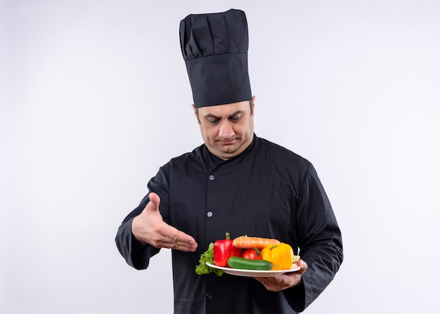 Chef masculino cozinheiro vestindo uniforme preto e chapéu de cozinheiro segurando o prato com legumes frescos, apresentando com o braço da mão em pé sobre um fundo branco