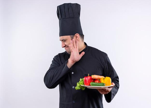 Chef masculino cozinheiro vestindo uniforme preto e chapéu de cozinheiro segurando o prato com legumes frescos e olhando para o lado com expressão de nojo em pé sobre um fundo branco