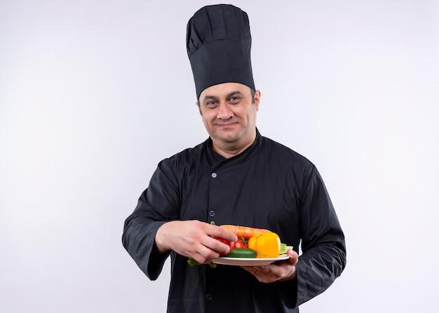 Chef masculino cozinheiro vestindo uniforme preto e chapéu de cozinheiro segurando o prato com legumes frescos, olhando para a câmera com um sorriso no rosto em pé sobre um fundo branco
