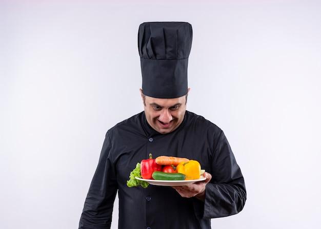 Chef masculino cozinheiro vestindo uniforme preto e chapéu de cozinheiro segurando o prato com legumes frescos, olhando para o prato com um sorriso no rosto em pé sobre um fundo branco