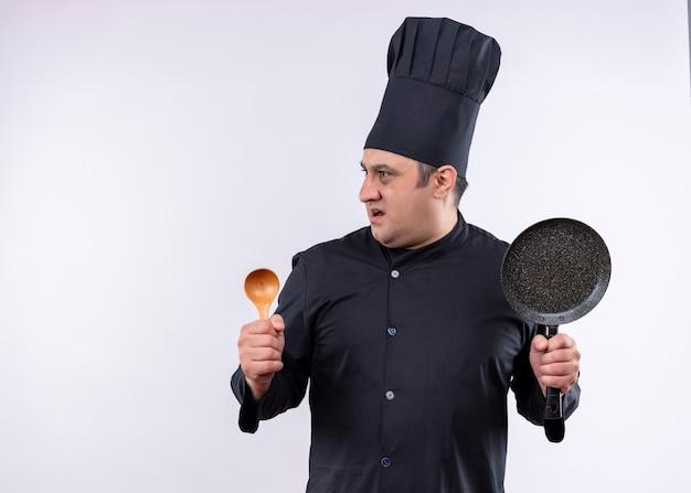 Chef masculino cozinheiro vestindo uniforme preto e chapéu de cozinheiro segurando uma colher de pau e uma panela, olhando de lado surpreso em pé sobre um fundo branco