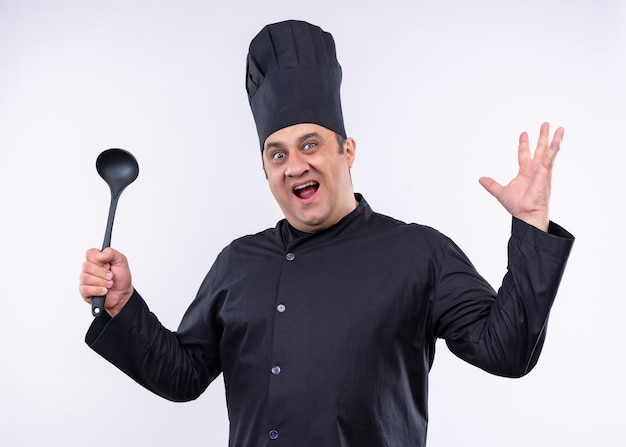 Chef masculino cozinheiro vestindo uniforme preto e chapéu de cozinheiro segurando uma concha, levantando o braço, olhando para a câmera com uma expressão agressiva em pé sobre um fundo branco