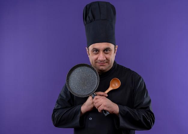 Chef masculino cozinheiro vestindo uniforme preto e chapéu de cozinheiro segurando uma frigideira e uma colher de pau cruzando as mãos olhando para a câmera sorrindo em pé sobre um fundo roxo