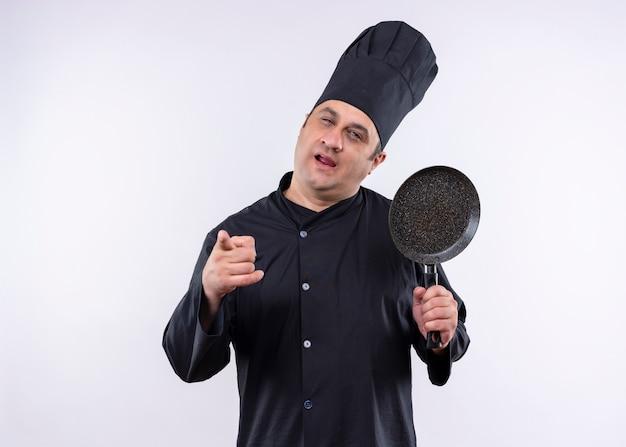 Chef masculino cozinheiro vestindo uniforme preto e chapéu de cozinheiro segurando uma panela apontando com o dedo para a câmera, feliz e positivo em pé sobre o fundo branco