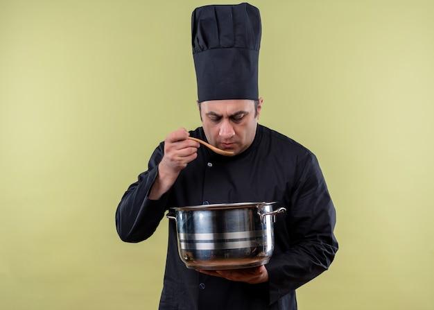 Chef masculino cozinheiro vestindo uniforme preto e chapéu de cozinheiro segurando uma panela, degustando comida com uma colher de pau em pé sobre um fundo verde