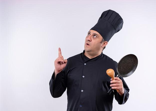 Chef masculino cozinheiro vestindo uniforme preto e chapéu de cozinheiro segurando uma panela e uma colher de pau apontando com o dedo indicador para cima surpreso em pé sobre um fundo branco