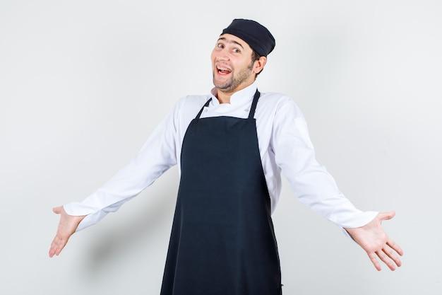 Chef masculino de uniforme, avental, abrindo os braços em um gesto de impotência e olhando alegre, vista frontal.