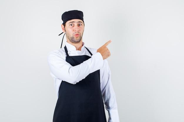 Chef masculino de uniforme, avental apontando o dedo para o lado e olhando surpreso, vista frontal.