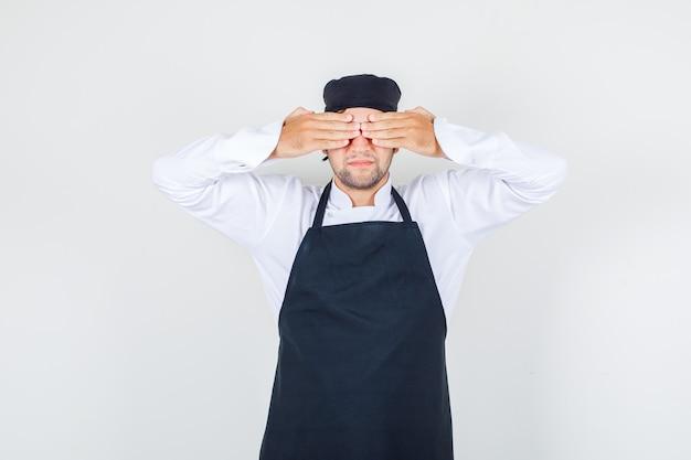 Chef masculino de uniforme, avental cobrindo os olhos com as mãos, vista frontal.