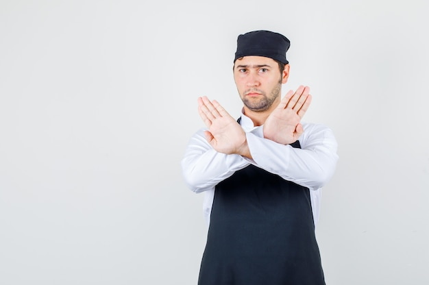 Chef masculino de uniforme, avental mostrando gesto de recusa e olhando sombrio, vista frontal.