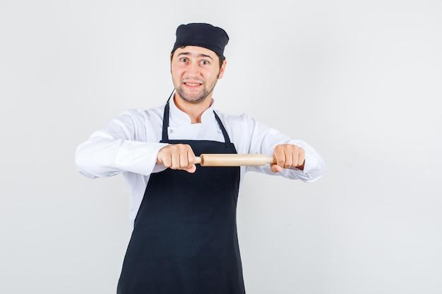 Chef masculino de uniforme, avental segurando o rolo e olhando alegre, vista frontal.