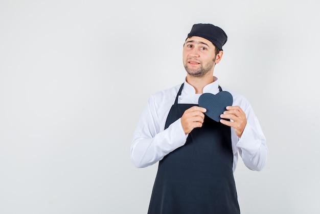 Chef masculino de uniforme, avental segurando uma caixa de presente preta, vista frontal.