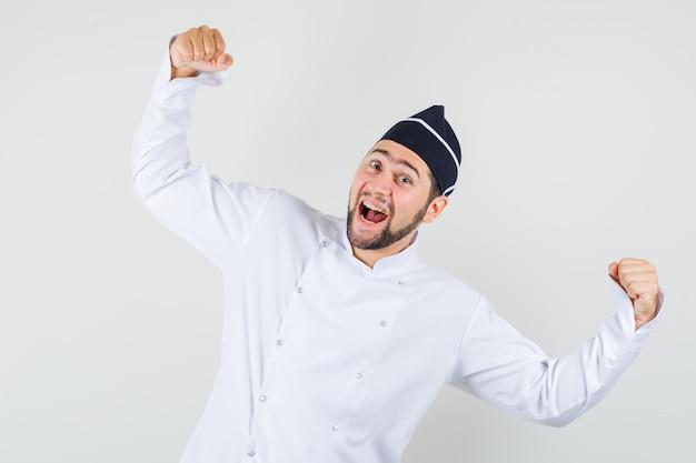 Chef masculino de uniforme branco, mostrando o gesto do vencedor e olhando alegre, vista frontal.