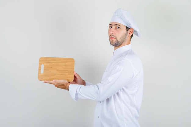 Chef masculino de uniforme branco segurando uma tábua de madeira e parecendo rigoroso