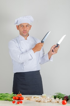 Chef masculino de uniforme, chapéu e avental segurando facas de metal na cozinha