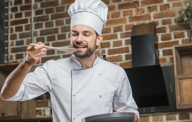 Chef masculino, degustação de comida na espátula de madeira