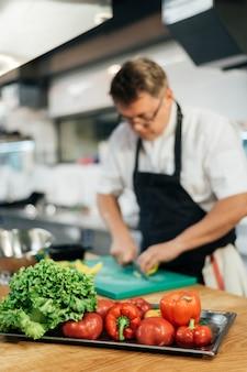 Chef masculino desfocado cortando vegetais