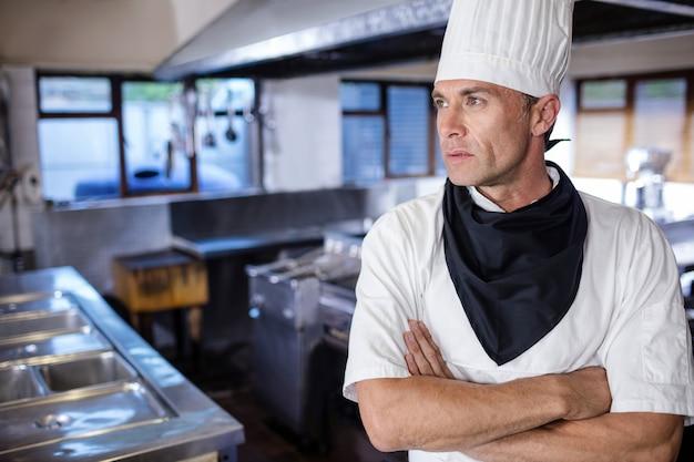 Chef masculino em pé com os braços cruzados na cozinha