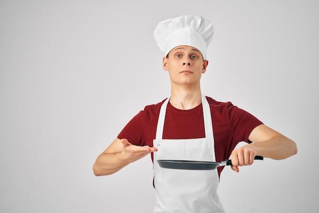 Chef masculino em uma frigideira de avental branco cozinhando comida