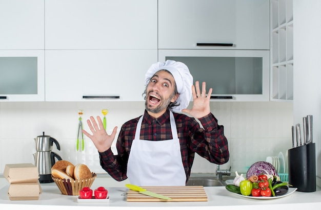 Chef masculino feliz de vista frontal abrindo as mãos na cozinha