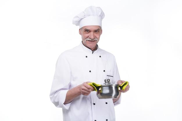 Chef masculino maduro sorridente com manto branco e tigela de metal nas mãos na parede branca