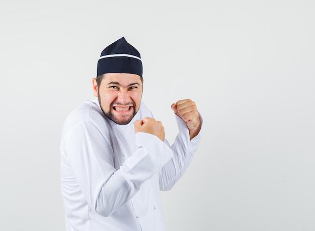 Chef masculino mostrando gesto de vencedor em uniforme branco e olhando feliz, vista frontal.