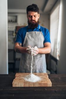 Chef masculino no avental com farinha nas mãos, trabalhando na tábua. cozinhar pão