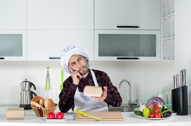 Chef masculino pensando em vista frontal segurando uma caixa de hambúrguer na cozinha