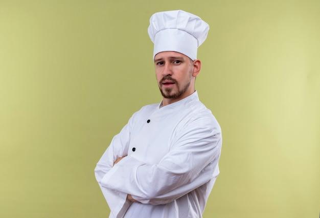 Chef masculino profissional satisfeito cozinheiro em uniforme branco e chapéu de cozinheiro em pé com os braços cruzados, parecendo confiante sobre um fundo verde