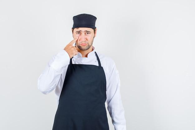 Chef masculino puxando para baixo a pálpebra de uniforme, avental e olhando triste, vista frontal.