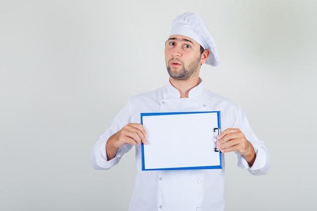 Chef masculino segurando a prancheta em uniforme branco e parecendo surpreso
