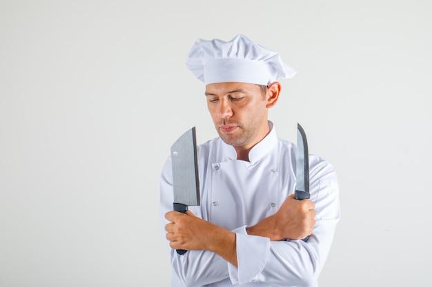 Chef masculino segurando facas com braços cruzados em uniforme e chapéu
